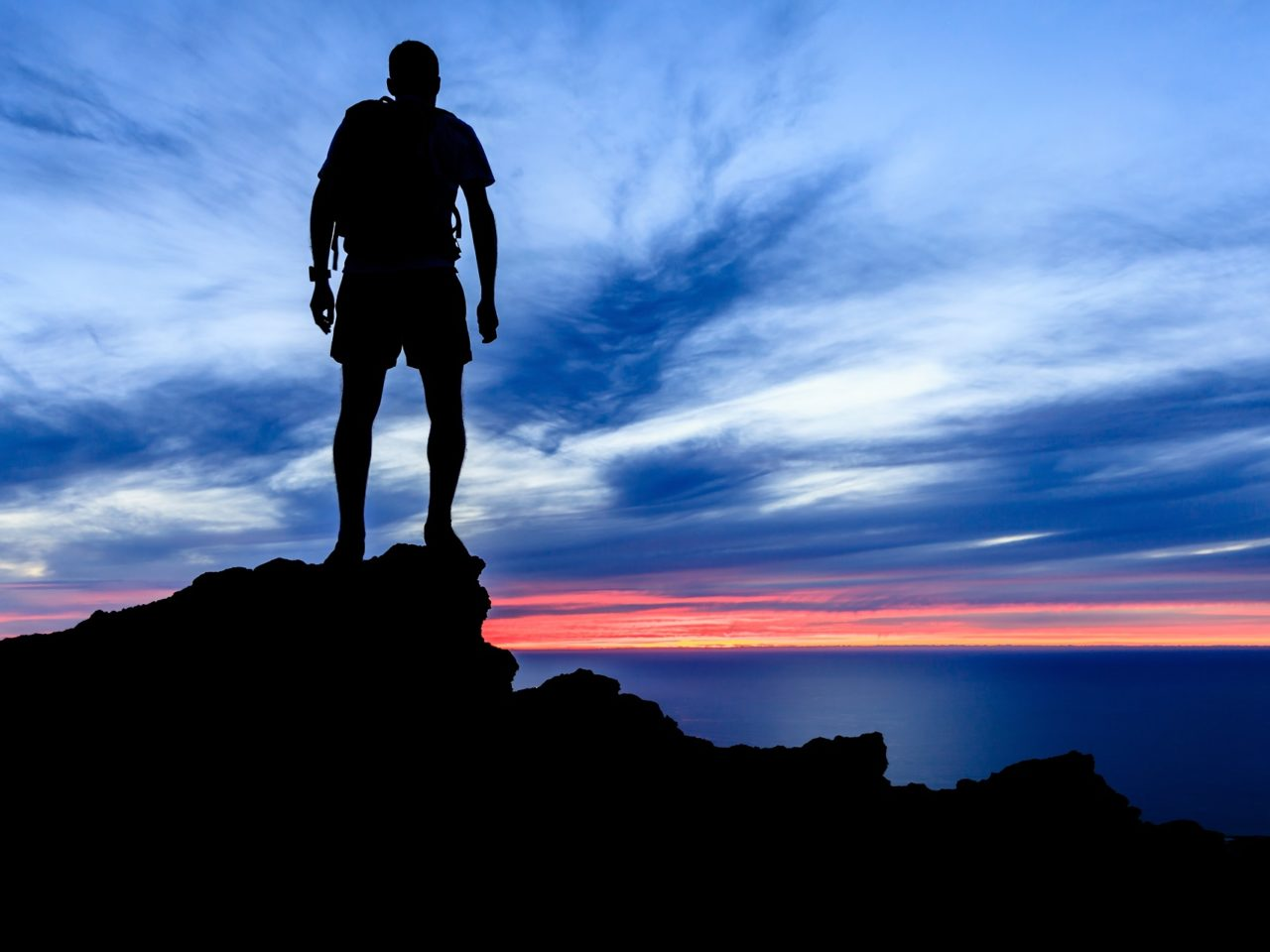 Man hiking silhouette in mountains, sunset and ocean over beautiful blue sky. Male hiker walking on top of mountain looking at beauty night landscape.